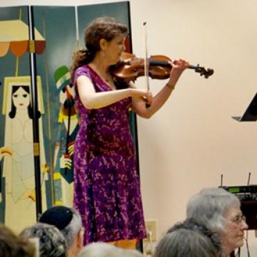 Gayna Bassin playing violin before an audience.