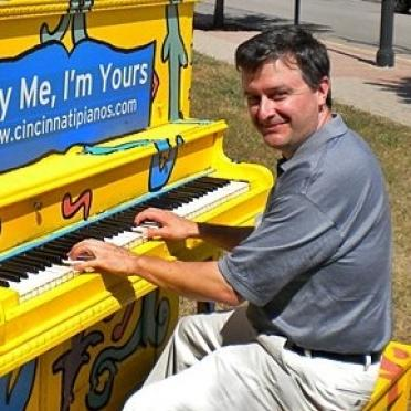 Richard Seil playing a yellow upright piano outdoors.