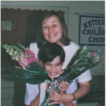 Valerie Bobosh with a young child and flower bouquets.